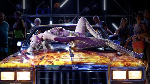 """""""Titane"""": Starke Frauen, schöne Autos: Alexia (Agathe Rousselle) räkelt sich auf der Motorhaube ihres geliebten Cadillacs."""